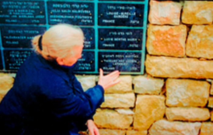 Yanina Ecker in the Righteous Among Nations Avenue in Yad Vashem pointing to the names of her Polish parents.